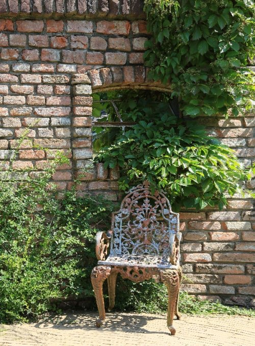 gu eiserner stuhl vor einer alten mauer. Black Bedroom Furniture Sets. Home Design Ideas