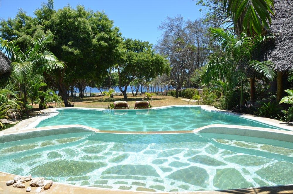 sonnenliegen an einem pool und im hintergrund das meer. Black Bedroom Furniture Sets. Home Design Ideas